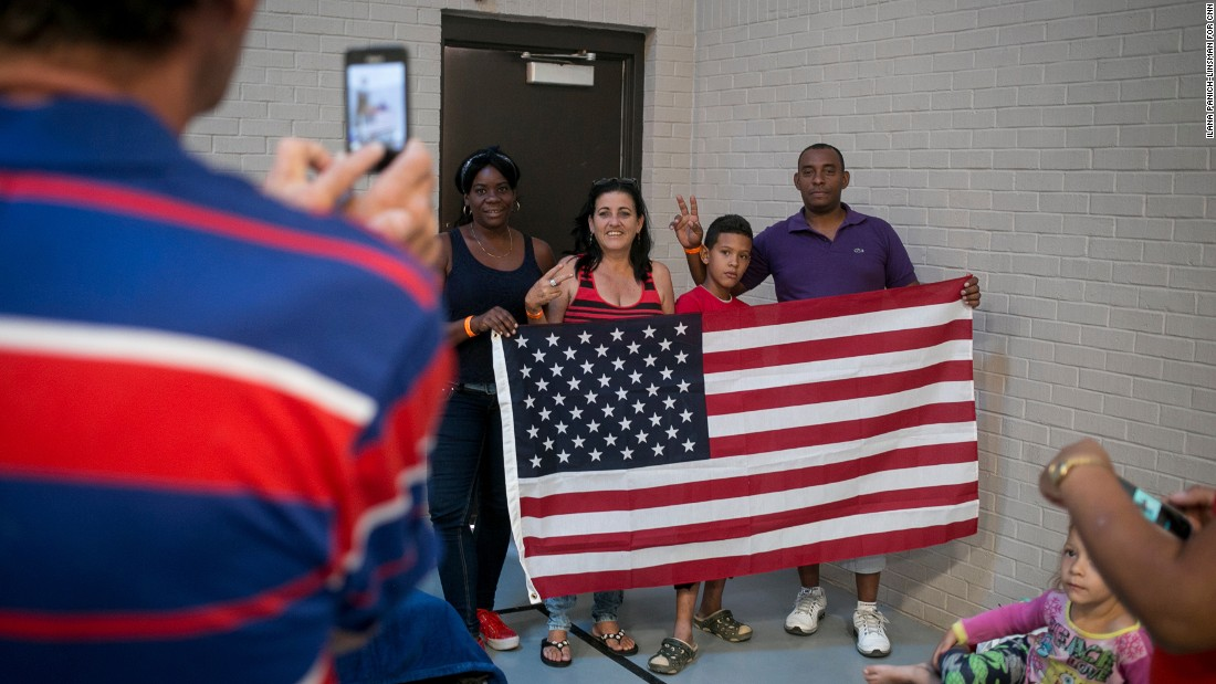 "As soon as Idael Rodríguez Rivas unfurled an American flag, people rushed to have their photos taken with it. ""Someone gave it to me,"" Rodríguez says. ""Someday, I'm taking it back to Cuba with me."" Here, Kenia Suarez Brunet, 39, Maria Nelys Casto Mirabal, 51, Yancarlos Rodriguez Castillo, 10, and Ismael Martinez Ramcoll, 40, pose for the camera."