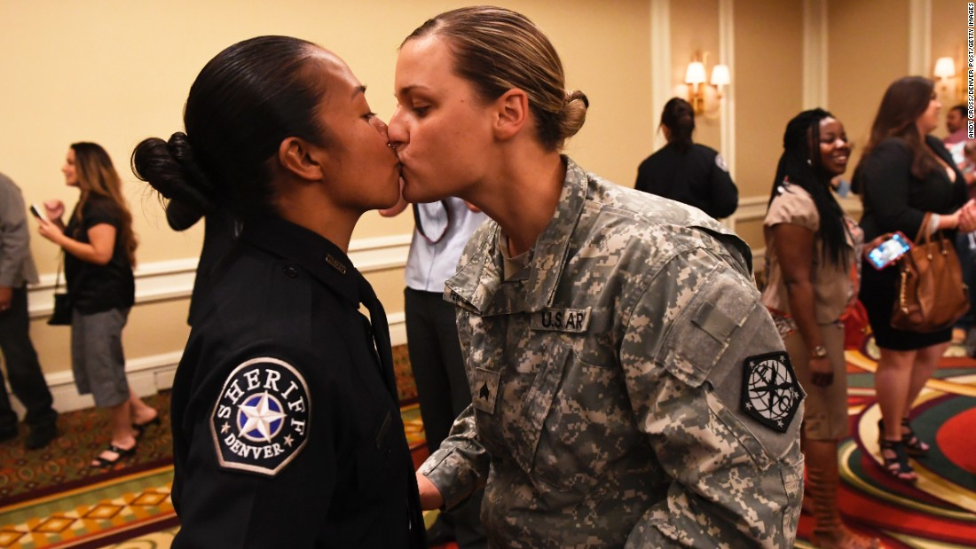 U.S. Army Sgt. Kathryn Fermin-Weinreb, right, kisses her wife, Victoria, after Victoria graduated from the Denver Sheriff Department training academy on Friday, May 13.