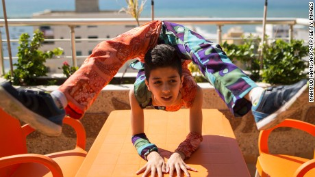 Palestinian teenager Mohammed al-Sheikh, 12, shows his skills on a table in Gaza city on April 28, 2016. Mohammed al-Sheikh is only 12 and feels trapped in Gaza but he dreams of a Guinness world record for a series of stunning backflips and his almost unbelievable body contortions. Mohammed, just 1.37 metres (four foot, six inches) tall and weighing 29 kilograms (64 pounds), can bend his body in seemingly impossible ways, throwing his feet over his shoulders with reckless abandon or jumping into a spider-like pose. / AFP / MAHMUD HAMS        (Photo credit should read MAHMUD HAMS/AFP/Getty Images)