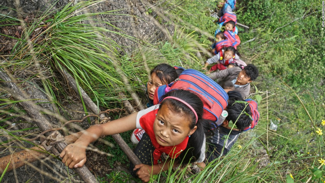 "Fifteen children ages 6 to 15 go to school at the foot of a mountain. They make the journey climbing the unsteady ""sky ladders,"" as locals call them."