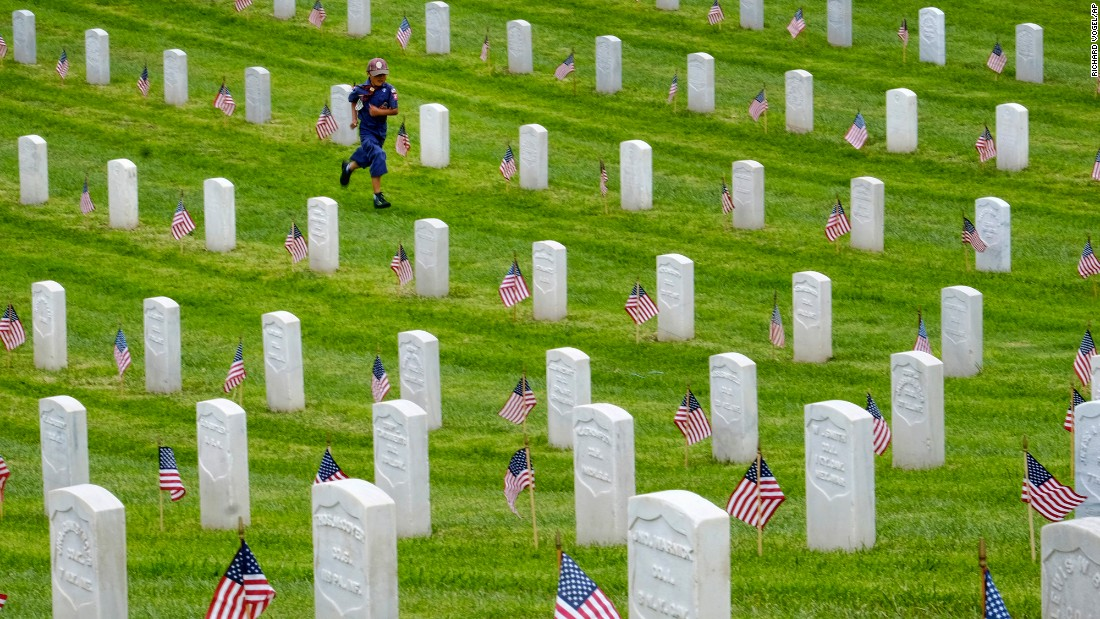 A Boy Scout runs past gravestones after volunteers placed American flags at the Los Angeles National Cemetery on Saturday, May 28.