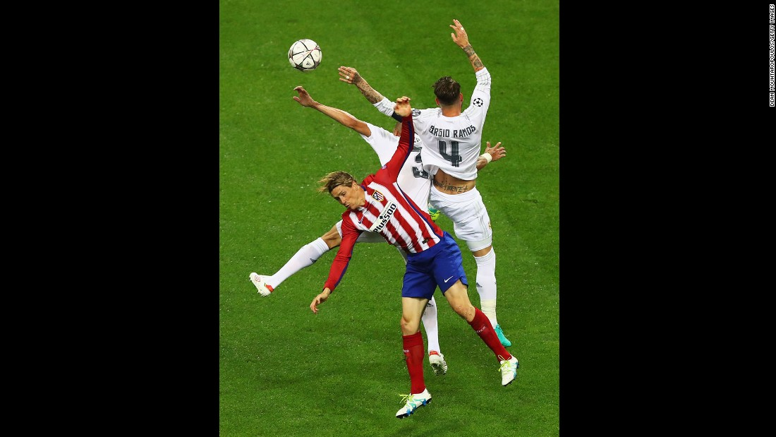 Fernando Torres of Atletico Madrid is challenged by Real Madrid's Sergio Ramos and Pepe.