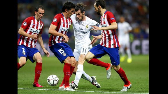 Real Madrid's Gareth Bale tries to maintain control of the ball while driving through some Atletico players.