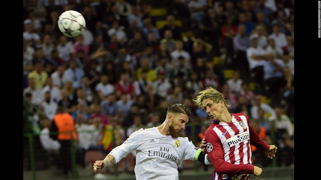 Atletico Madrid forward Torres heads the ball past Real Madrid defender Ramos.