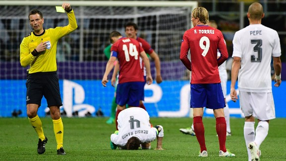 Atletico Madrid forward Torres receives a yellow card from referee Clattenburg as Ramos lies on the ground.
