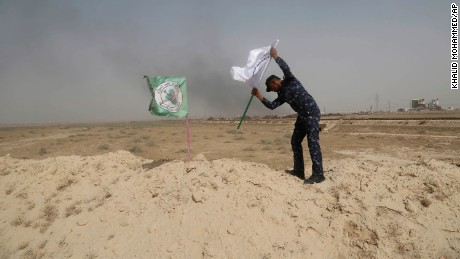 A policeman places an Iraqi federal police flag next to a Shiite Popular Mobilization Forces flag outside Falluja on May 28.