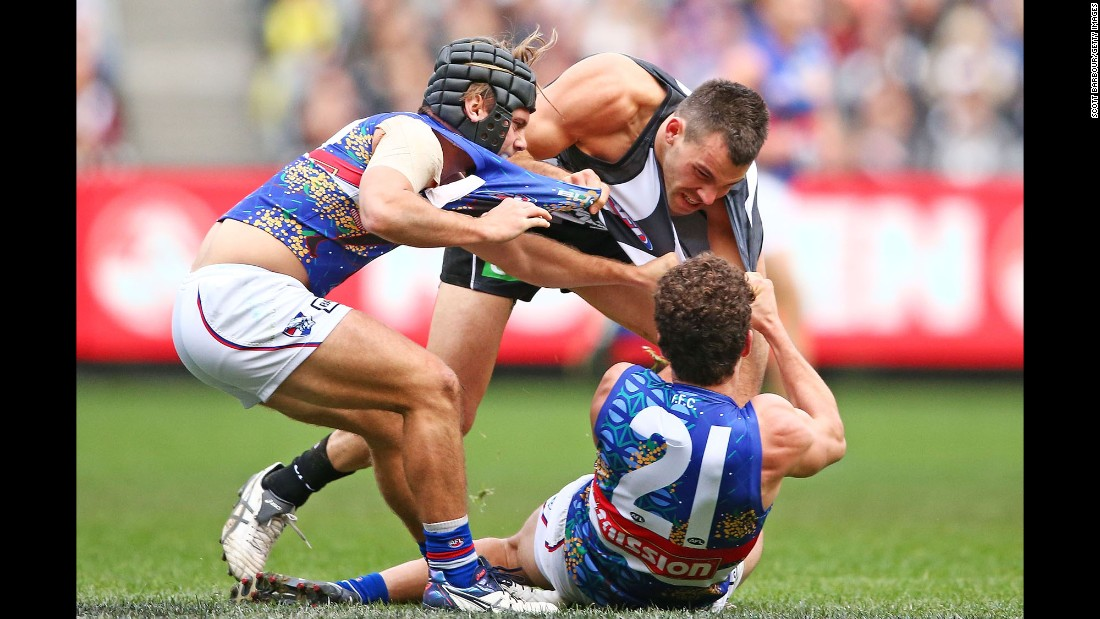 A couple of the Western Bulldogs tackle Levi Greenwood of the Collingwood Magpies during an Australian Football League match on Sunday, May 29.