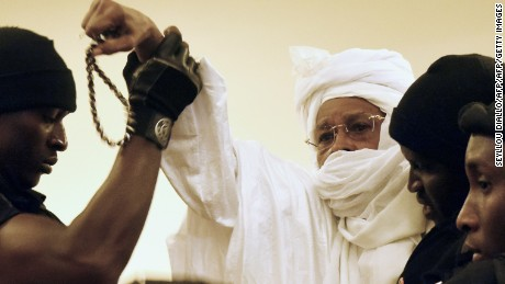Prison guards escort ex-Chadian dictator Hissene Habre into court when his trial first began in July in Dakar, Senegal.