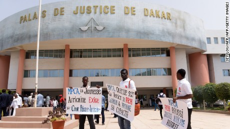 Activists stand outside the courthouse in Dakar before Monday's verdict.