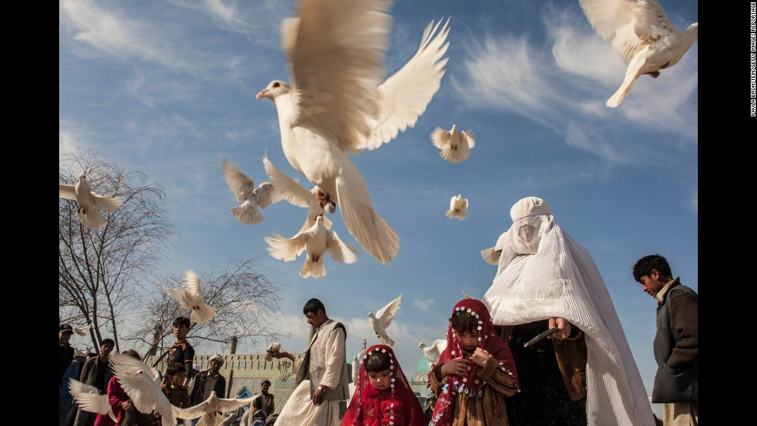 A family feeds pigeons at the Blue Mosque in Mazar-e-Sharif, Afghanistan, in November 2009.
