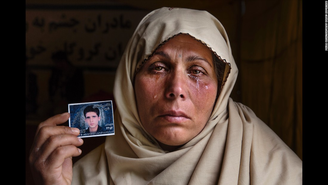 Bibi Aisha cries in April 2015 as she holds a photo of her 22-year-old son, Yousef, who was kidnapped. After many weeks with no answer, she worried he would be killed.