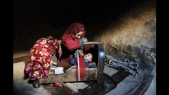 A mother tends to her son inside their home in Afghanistan's Wakhan Corridor in October 2007.