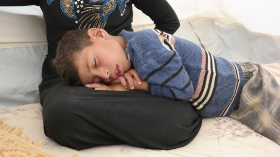 Aus, 7, sleeping on his mother's lap at a refugee camp in Iraq