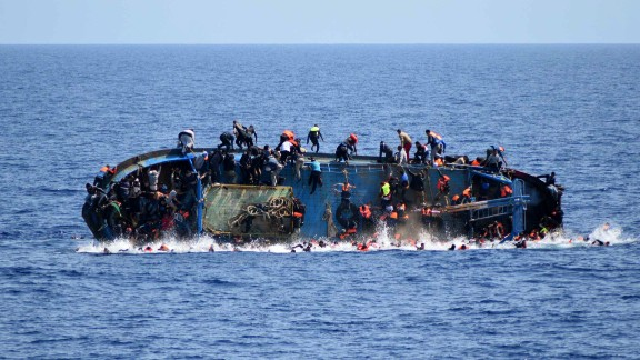 A ship crowded with migrants flips onto its side in May 2016 as an Italian navy ship approaches off the coach of Libya. Passengers had rushed to the port side, a shift in weight that proved too much. Five people died and more than 500 were rescued.
