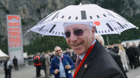 A guest poses with an umbrella decorated with the Swiss Rail clock logo before the opening ceremony of the Gotthard Base Tunnel.