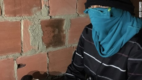 A young gang member masked his face and refused to reveal his name for fear of being identified by Brazilian authorities.