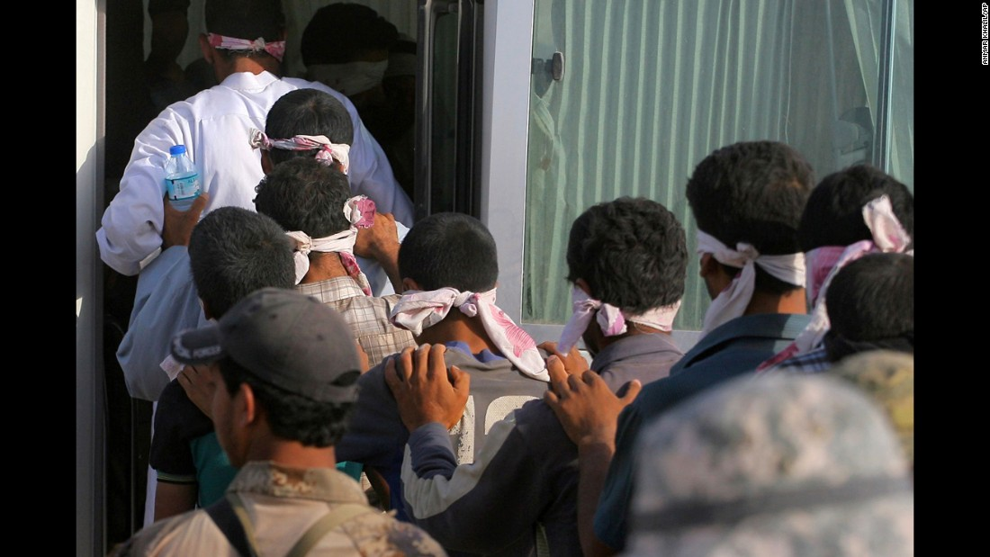 Blindfolded men get led to a bus after being detained during the fighting on June 1.