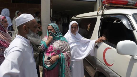 Pakistani relatives stand alongside an ambulance carrying Maria Abbasi, June 1, 2016.