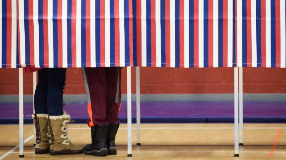 A voter with a child casts their ballot on February 9, 2016 at Broken Ground School in Concord, New Hampshire.