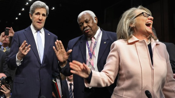 Sen. John Kerry talks with committee staffer Bertie Bowman as U.S. Secretary of State Hillary Clinton attends Kerry