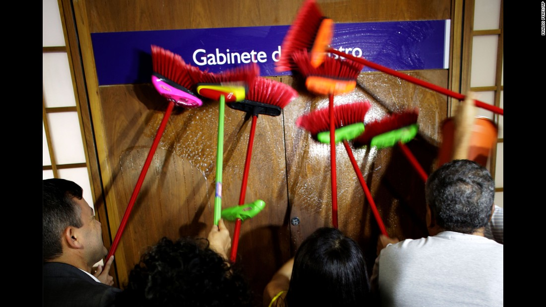 "Ministerial staff members use brooms to scrub the office door of Brazilian Transparency Minister Fabiano Silveira, demanding his resignation on Monday, May 30. The day before, <a href=""http://money.cnn.com/2016/06/01/news/economy/brazil-recession-economy/"" target=""_blank"">leaked phone call recordings</a> showed Silveira -- who was appointed to combat corruption -- advising a senator on how to dodge a corruption probe. Silveira resigned Monday. Protesters in Brazil use brooms as a symbol to sweep away corruption."