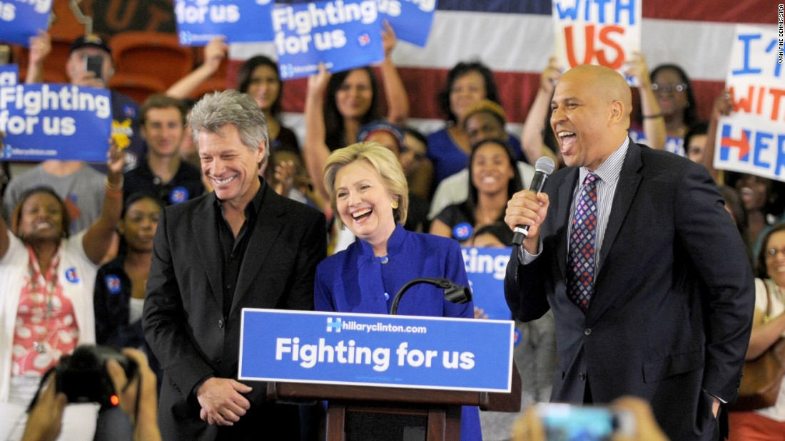 Rock star Jon Bon Jovi, left, stands on stage with Democratic presidential candidate Hillary Clinton and U.S. Sen. Cory Booker before Clinton spoke at a rally in Newark, New Jersey, on Wednesday, June 1.