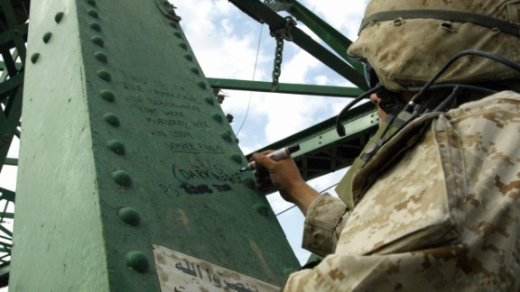 During the second battle of Falluja in November 2004, a Marine writes a message on the bridge over the Euphrates where the charred bodies of American contractors were hung.