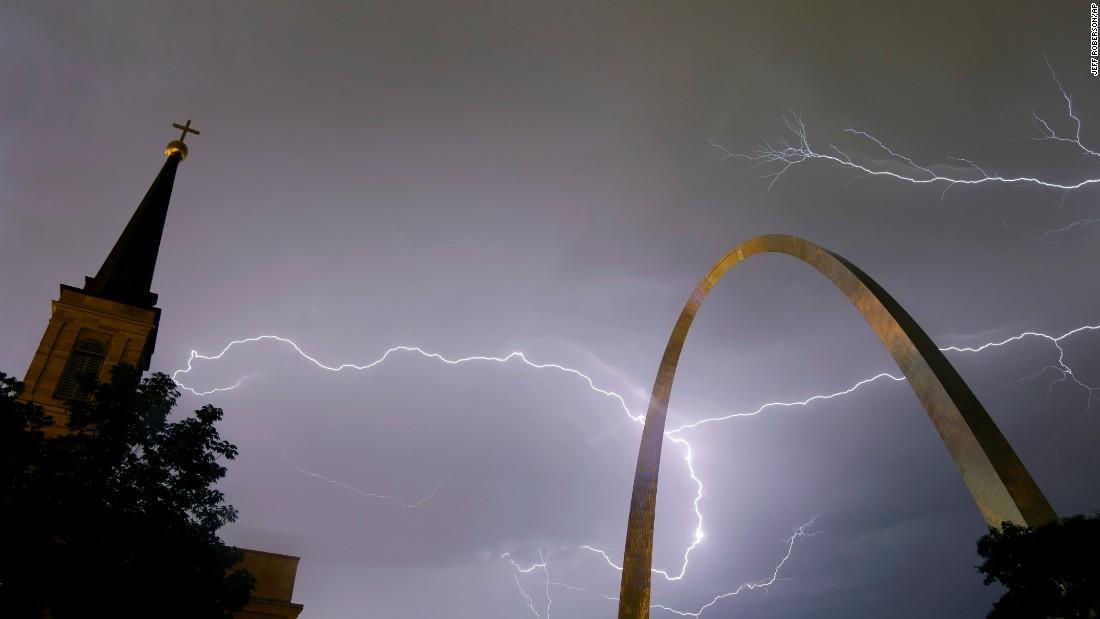 Lightning flashes in the sky behind the Gateway Arch and the Old Cathedral in St. Louis on Wednesday, May 11. The storm left thousands without power.