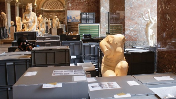 Plastic boxes containing artworks are placed between sculptures for safe-keeping in an exhibition hall at the Musée du Louvre on June 3.