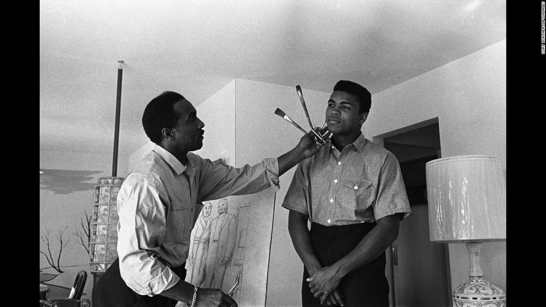 Ali poses in 1963 while his father works on a portrait.