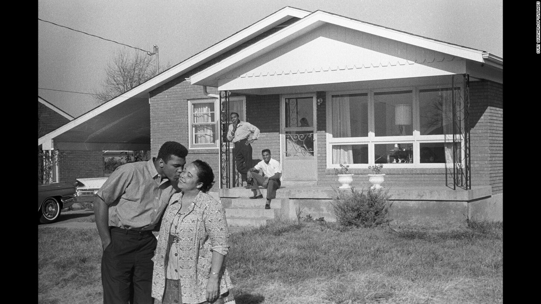 Muhammad Ali, whose birth name was Cassius Clay, kisses his mother, Odessa, in front of the family's Louisville, Kentucky, home in 1963, as his father, Cassius Clay Sr., and brother, Rudy, look on.  Ali changed his name in 1964 after converting to Islam.