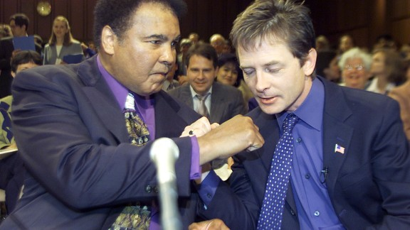 Muhammad Ali and Michael J. Fox talk before the start of a Senate subcommittee on Labor, Health, Human Services and Education hearing on Parkinson's Disease in May 2002 in Washington, DC.