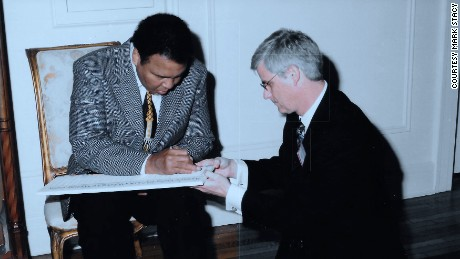 Muhammad Ali signed a WHO petition to support a global initiative to find a cure for Parkinsons in 2003, with Dr. Mark Stacy holding the document.