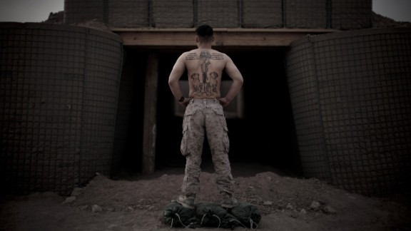 3rd Battalion, 6th Marines, Sgt. Paul Williams shows his tattoos at the entrance to a bunker at a base in Afghanistan on March 20, 2010.