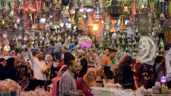 Egyptians walk past traditional lanterns in the Saida Zeinab district of Cairo on Sunday, May 29.