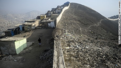 "Picture of the so-called ""Wall of Shame"" in the outskirts of Lima on April 08, 2016.  The place began to be populated 20 years ago, with migration of Andean people displaced by poverty and violence of the guerrillas from the countryside to the city. The 10km length wall separates dusty huts without electricity or water from mansions with pool and green areas, recalling that economic growth is not for everyone. / AFP / ERNESTO BENAVIDES        (Photo credit should read ERNESTO BENAVIDES/AFP/Getty Images)"