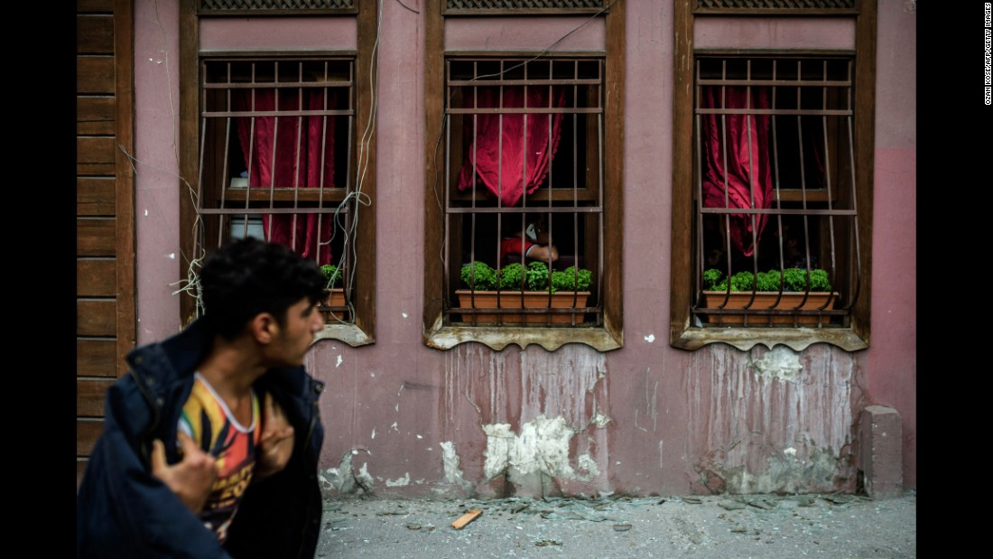 A man walks past a building with broken windows from the blast.