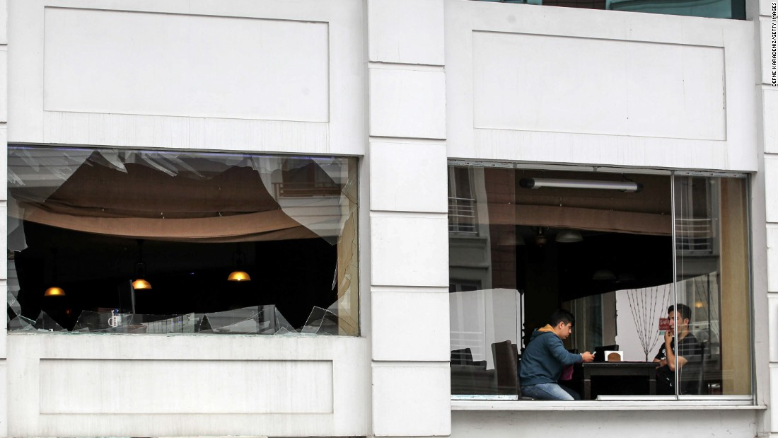 Two men sit near the broken windows of a restaurant as police officers secure the area.