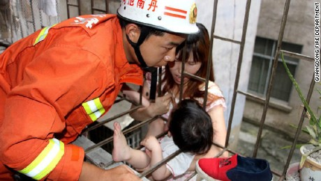 Firefighters in China rescued a three-year-old girl who fell through a gap in a second-floor balcony.