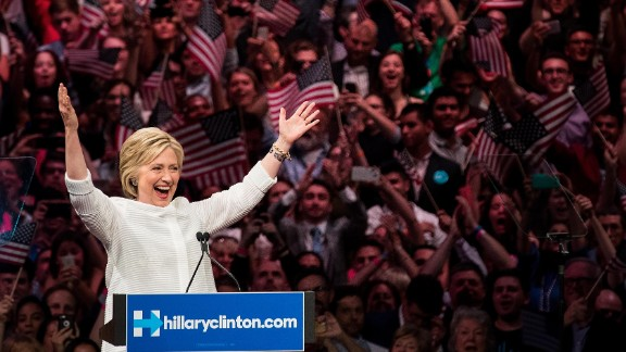 Democratic presidential candidate Hillary Clinton gestures to the crowd at the start of her remarks during a primary night rally at the Duggal Greenhouse in the Brooklyn Navy Yard, June 7, 2016 in the Brooklyn borough of New York City. Clinton  has secured enough delegates and commitments from superdelegates to become the Democratic Party