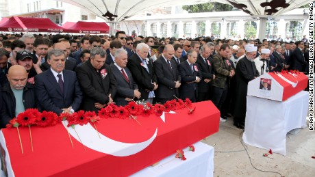 Turkish Prime Minister Binali Yildirim and former Turkish President Abdullah Gul attend the funeral ceremonies of two police officers killed Tuesday.