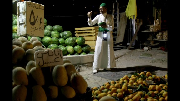 """A man in Sidon, Lebanon, wakes up Muslims for their overnight """"suhur"""" meal before the day's fast on June 8. During Ramadan, Muslims fast from dawn until dusk."""