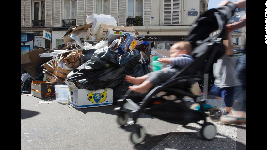 A Parisian pushes a stroller in front of rubbish bins in the Pigalle district on June 9.