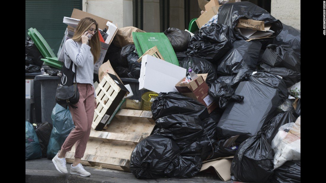 A woman walks past a pile of uncollected rubbish. There has also been a surprise blockade of supply trucks at the main food terminal for the Paris region.