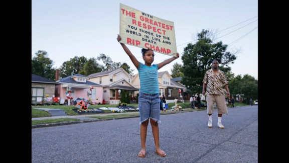 Akera Price-King, 9, carries a sign in front of Ali's childhood home.