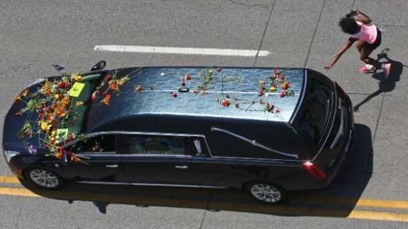 A girl rushes to touch the hearse carrying Ali's body.