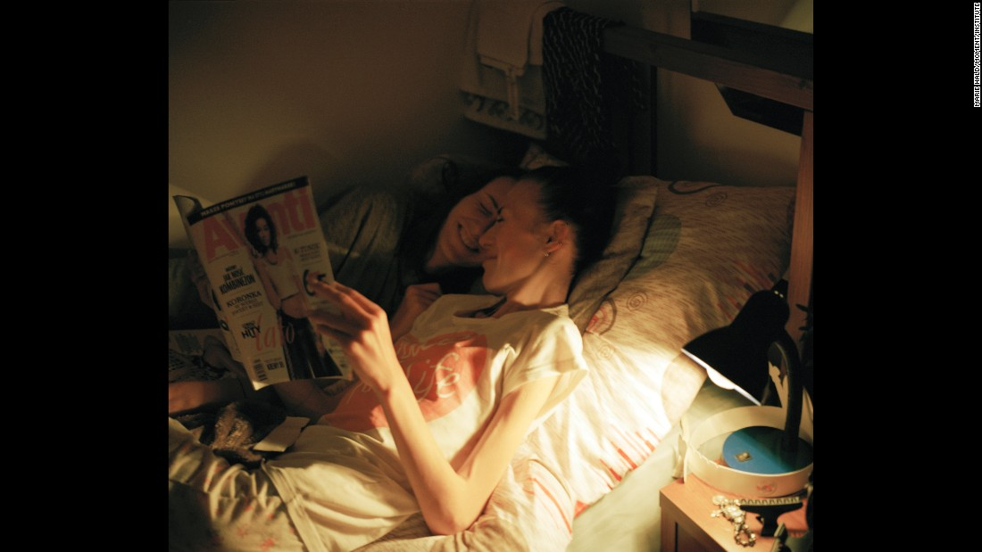 Karolina and Kaia sneak into the same bed and read magazines together one night.