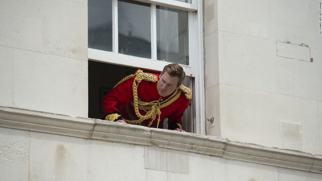 A soldier looks out of an upper floor window to watch the parade.