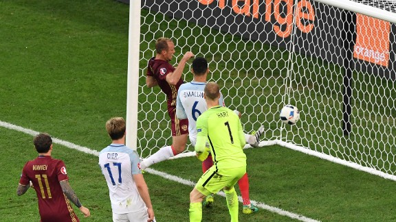 England's goalkeeper Joe Hart, center, looks at the ball going into his net as Russia scores at the end of the game.  Russia's 92nd minute equalizer denied England victory.