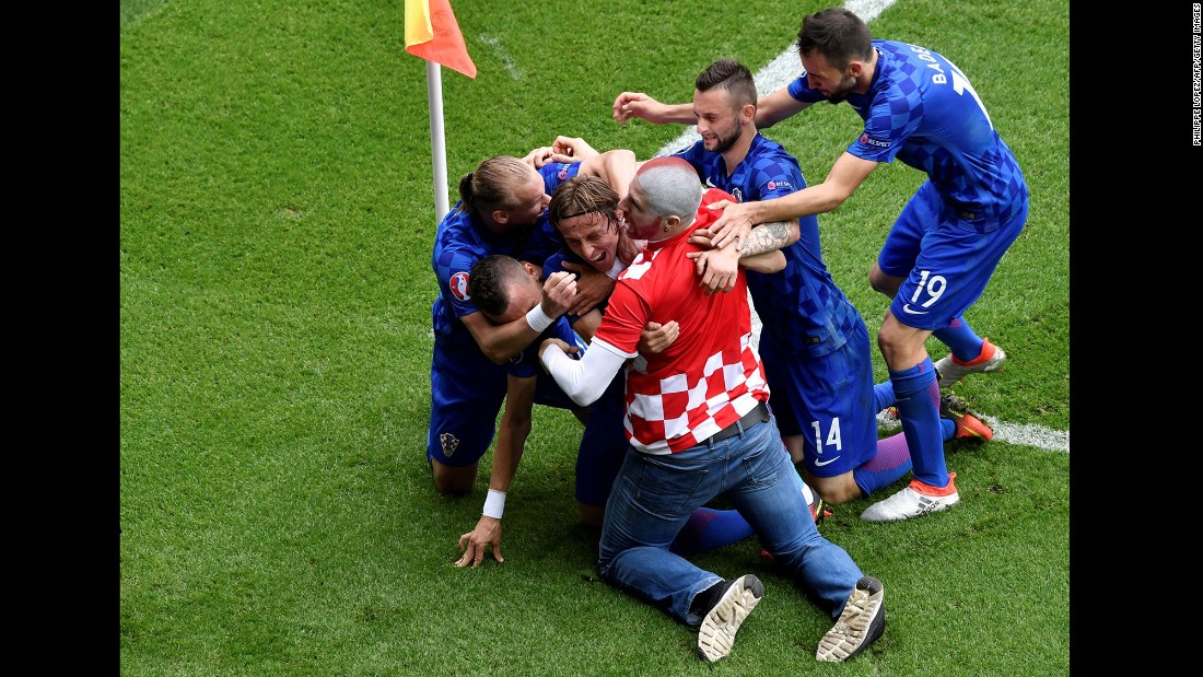 A fan enters the pitch to celebrate with Modric after the goal.
